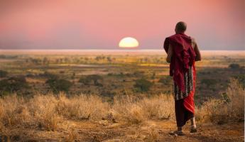 A Maasai warrior walks across the African bush