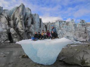 Family sitting on a glacier.