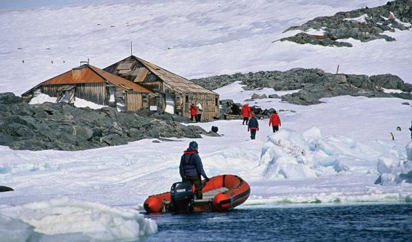 Visitors hike up to Mawson's Huts at at Cape Denison.