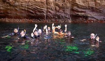 Travelers snorkeling in the beautiful Galapagos waters.