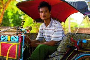 Man sitting in his rickshaw.
