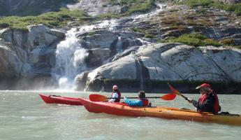 Kayaking past a waterfall.