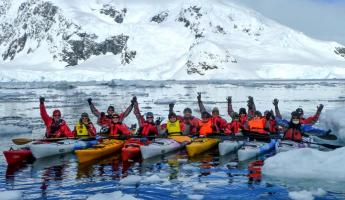 A group of kayakers pose in the icy waters of Antarctica.