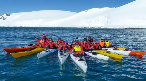 Kayakers pose in formation for the camera.