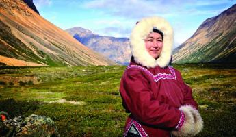 A local stands in traditional dress for the arctic.