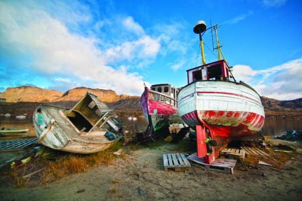 Abandoned boats resting on the shore.