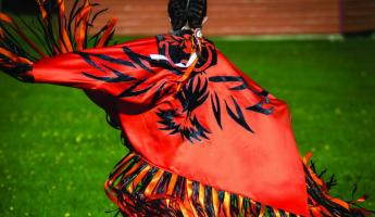 A local in native dress dances in traditional style.