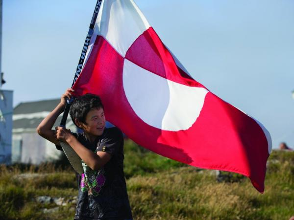 A local boy carries the flag of Greenland.
