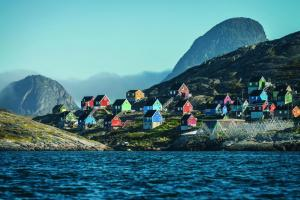 An arctic village full of colorful houses sits on the arctic coast.