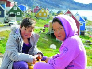 Local girls sit in front of colorful houses in their village.