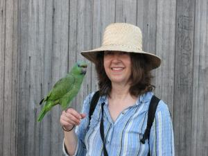 A traveler makes friends with a parrot.