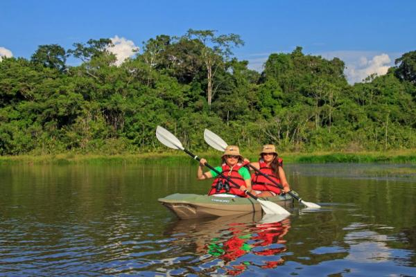 Two kayakers making their way down the Amazon River.