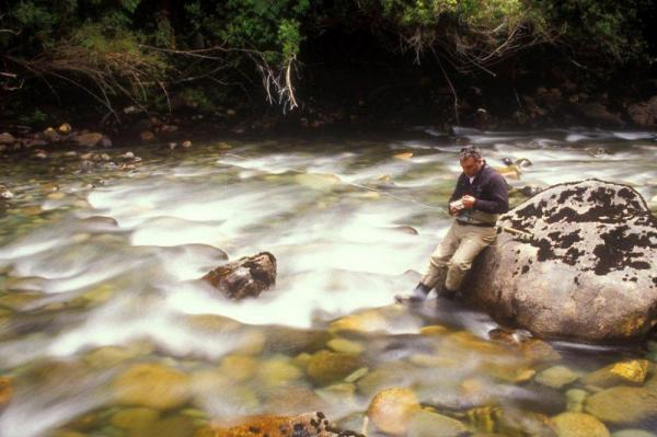 A fly fisherman changes his fly in the rushing river water.