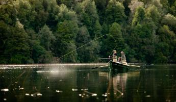 Two fly fisherman attempt a catch in their boat.