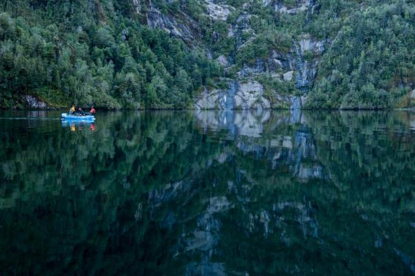 Travelers out in a raft in beautiful reflective waters.