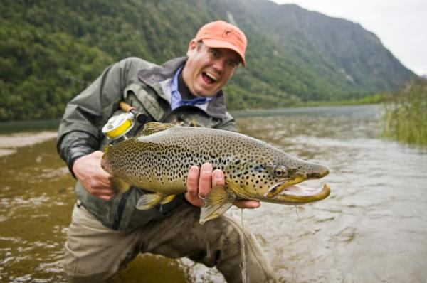 A fly fisherman show off his catch to the camera.