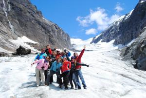 Travelers pose at the base of a glacier.