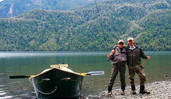 Two fly fisherman pose next to their boat.
