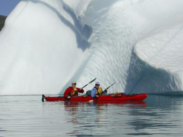 Kayaking in front of a huge iceberg.