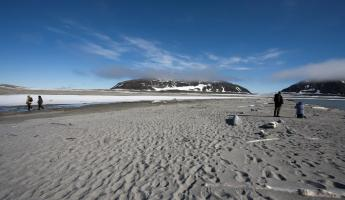 Travelers walking across the beaches of Spitsbergen.