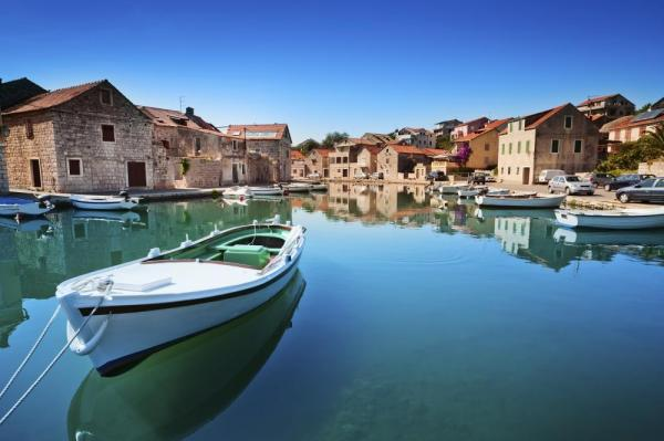 A boat sits in the still water outside a small eastern European town.