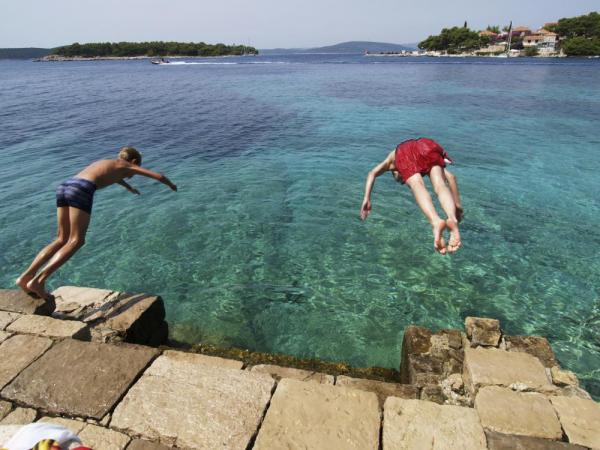 Two boys take a dive off the rocks.