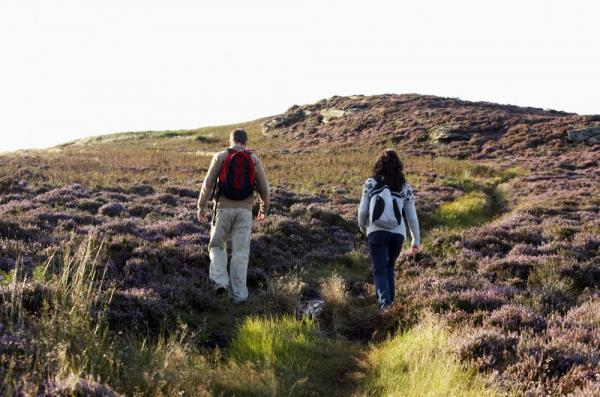 Hikers make their way up the rolling hills of the British Isles.