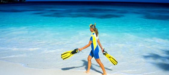 A snorkeler walking along a white sandy beach.