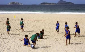 Young children playing soccer on the beach in Brazil