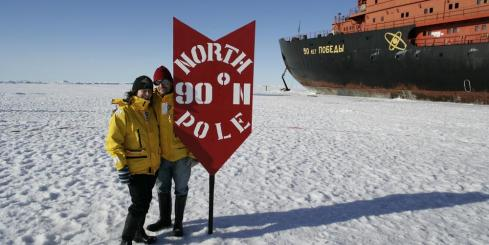 Travelers standing next to the North Pole.