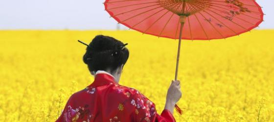 A young woman walks through a field of flowers