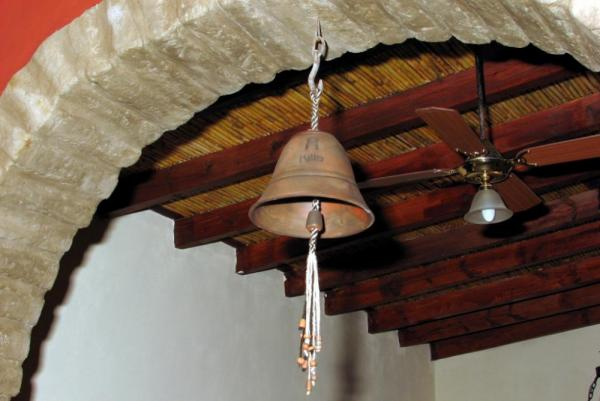 A bell hangs in the doorway of the Killa Cafayate.