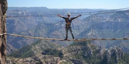 A traveler crossing a bridge over Copper Canyon.