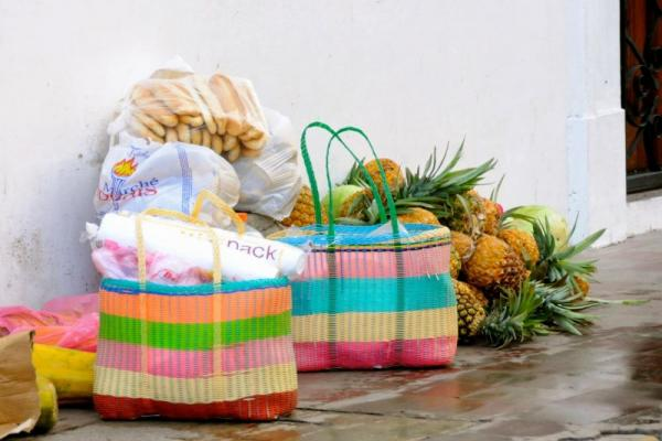 Sacks of groceries including a pile of pineapples sit on the ground.