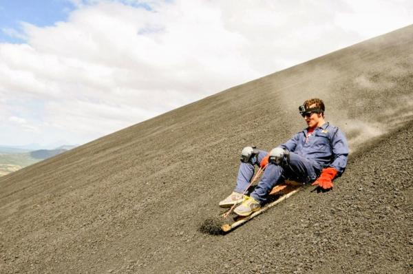 A traveler sand boards down the Cerro Negro Volcano.