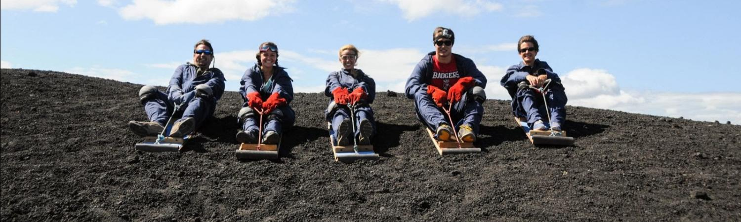 A family waiting to start sand boarding down a volcano.