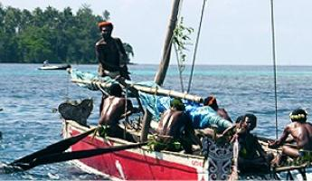 Traditional fishing boats sail the waters off the coast of New Guinea