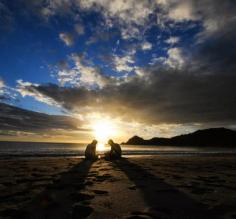 The sun sets behind two travelers enjoying the warm sands of a Nicaragua beach.