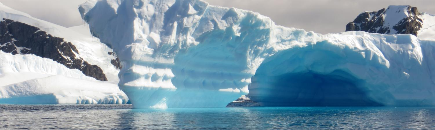 Beautiful blue icebergs emerge from the ocean.