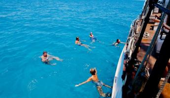 Swimming of the side of the Liberty Clipper in the crystal clear waters.