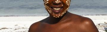 A local woman wears traditional face paint that protects the face from sun and mosquitoes.