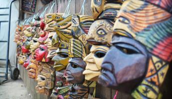 Traditional masks of Chiapas line a wall.