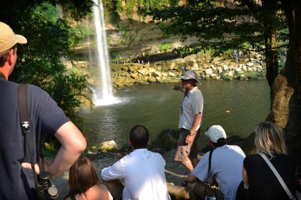 A guide informs visitors about the beautiful Misol-Ha waterfall.