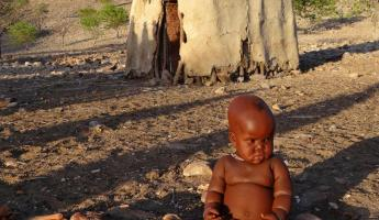 A young child sits in front of a African hut