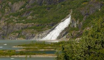 A large waterfall cascades from the Alaskan mountainside