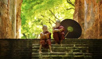 Two young monks read on the steps of a temple