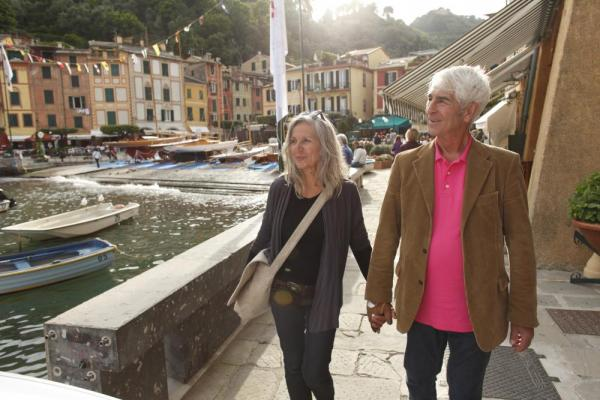 A couple walks through a romantic harbor in Europe