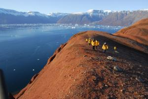 Hike along Eastern Greenland's red earth hills to gaze down at the iceberg-filled seas.