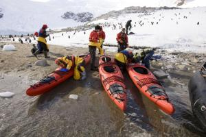 Travlers prepare to kayak while penguins look on