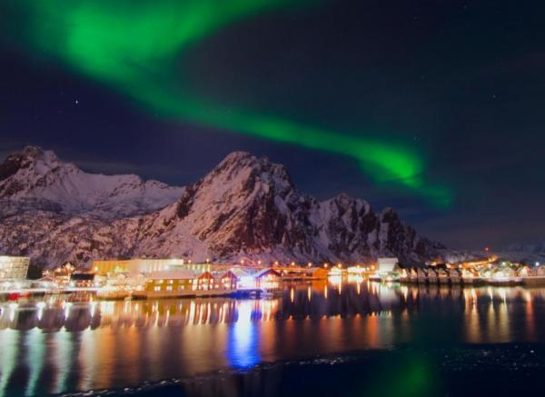 The mystical northern lights dance over a small Norwegian town